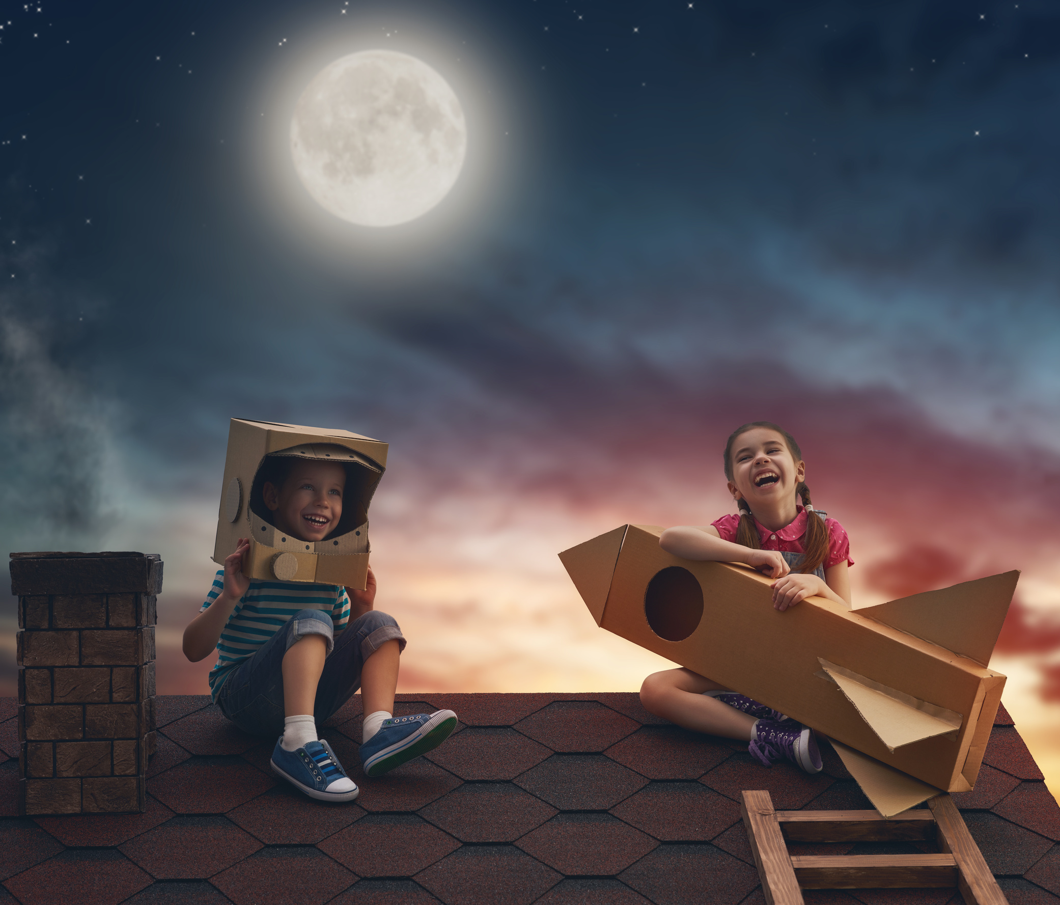 Two little children playing astronauts. Children on the background of moon sky. Child boy in an astronaut costume and child girl with toy rocket standing on the roof of the house and looking at the sky and dreaming of becoming a spacemen.