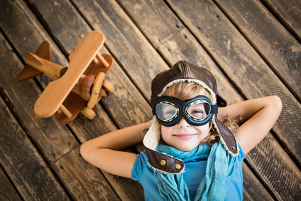 Child pilot with vintage plane toy on grunge wooden background